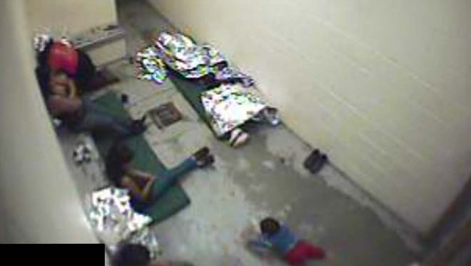 Women and children, some with mats, sit on a concrete floor in the U.S. Border Patrol's Douglas detention facility in September 2015.