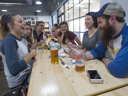 From left, Kayla Thomas, L'amour Johnson, Patrick McNeill, Lindsey Taylor, Chelsey Urdahl and Bradley Reider react to a question Wednesday, July 12, 2017, during a Geeks Who Drink pub quiz at Intersect Brewing in Fort Collins, Colo.