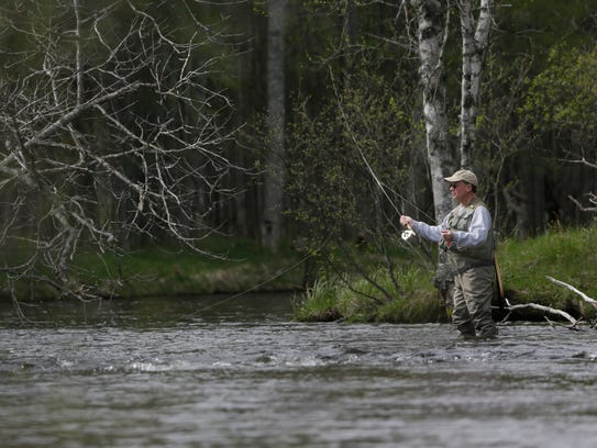 A fly fisherman casts his line in the north branch