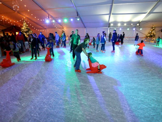 People make their way around the new ice skating rink during Christmas in the Garden, Friday, November 20, 2015, at the Oregon Garden in Silverton, Ore.