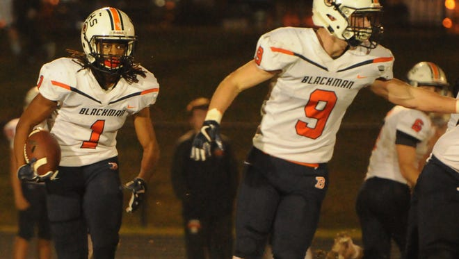 Blackman's Adonis Otey (1) runs behind the block of Connor Murphy (9) during  Friday's 38-7 win over Hendersonville in the first round of the 6A state playoffs. The Blaze battle at Oakland in round 2.