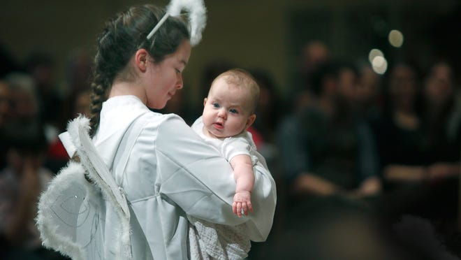 Brigid Marron, 12, of Penfield, as the Angel Gabriel brings four-month-old Naomi Rose DeLuca as Baby Jesus to Mary during the pageant Wednesday at Sacred Heart Cathedral.