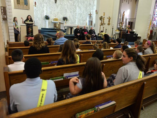 Bishop Schad Regional School eighth grade student Samantha Reuss, 14, of Vineland (top left) reads during a special prayer service honoring school principal Dr. Patrice DeMartino at Sacred Heart Church, Tuesday, Feb. 2 in Vineland.