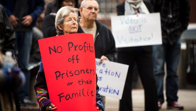 Members of the community hold signs calling on the sheriff to immediately bring back in-person visits to the Knox County jail during a rally held outside the City-County Building in downtown Knoxville on Monday, January 29, 2018.