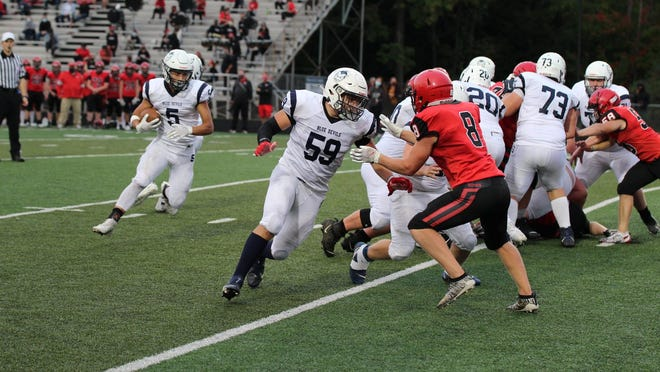 Sault High's John Robinson (5) looks for a block from Daylan Lujan (59) during a football game at Marquette Friday night. The Blue Devils beat the Redmen 22-16.