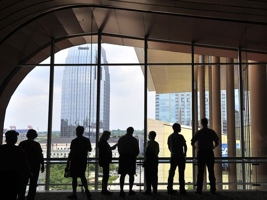Visitors are silhouetted as they look at downtown through the window at the opening of the Music City Center on May 19, 2013.