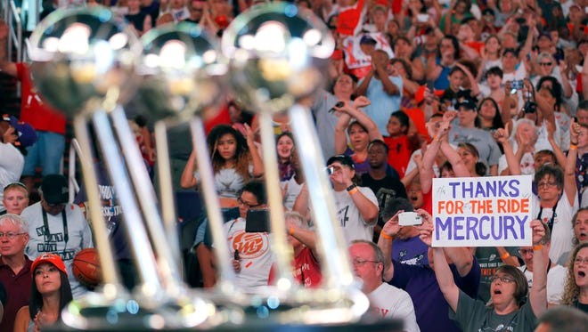 Phoenix Mercury fans celebrate behind their three championship trophies, during the Mercury championship celebration rally for their 2014 WNBA championship on Sunday, Sept. 14, 2014, in Phoenix.