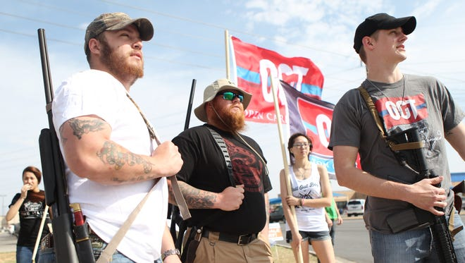 T.J. Holt, Kyle Carter and Tyler Benbow take part in an Open Carry Texas march in San Angelo, Texas in 2014. A proposal allowing Texans to openly carry handguns without permits is eligible for a Texas House floor vote.
