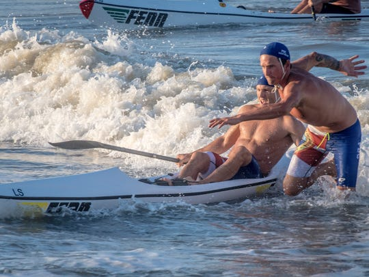 Matthew Lynskey on surfski passes off to Lexnar May to run the finish of the Taplin Relay.
