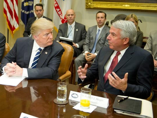 President Donald Trump listens to Robert J. Hugin,