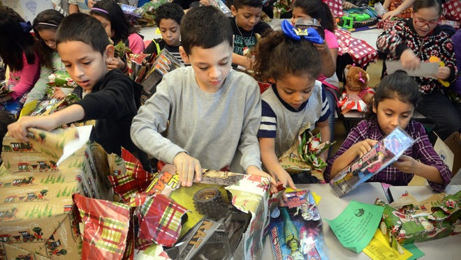 Peter Hernandez, 7 (from left); Christopher Mahan, 6; Myah Riojas, 6; and Rosilyn Reyes, 7; tear into their Christmas presents Wednesday, Jan. 4, 2017, during a Christmas gift distribution at Oak Park Elementary School. The event had to be rescheduled after the December tap water ban forced schools to close.