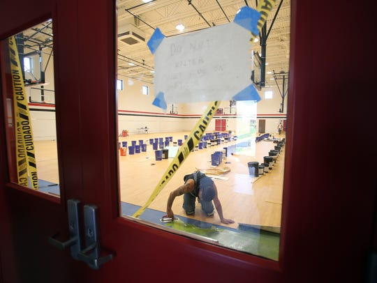 Workers work on the floors in the new gym at Dominican