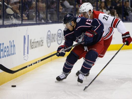 Columbus Blue Jackets' Cam Atkinson, left, carries the puck behind the net as Carolina Hurricanes' Brett Pesce defends during the second period of an NHL hockey game Friday, Nov. 10, 2017, in Columbus, Ohio. (AP Photo/Jay LaPrete)