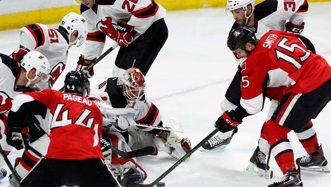 Devils goaltender Keith Kinkaid (1) keeps his eyes on the puck as Ottawa Senators' Zack Smith (15) prepares to shoot during the third period Saturday.