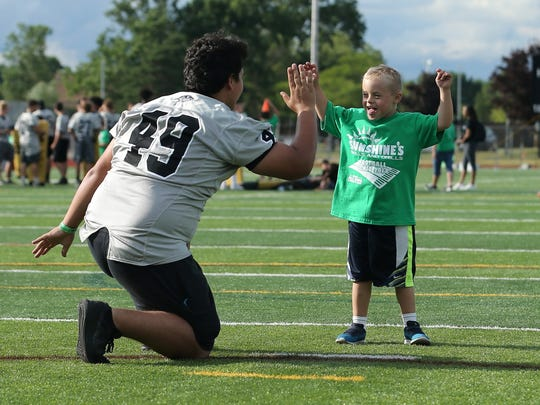 It's good! Max Robertson, 7, raises his arms in triumph after kicking the ball at the Sunshine's clinic. His buddy is Plymouth junior Sean Britt (49).