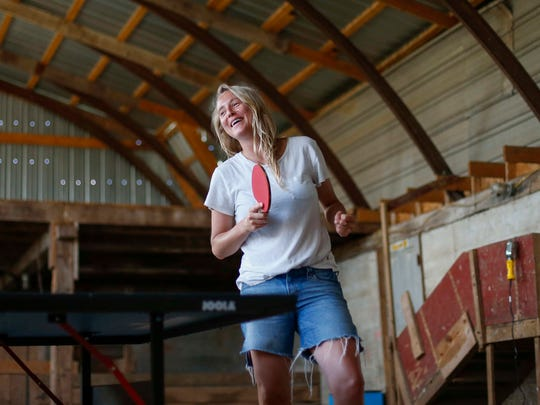 Lissie Maurus, a folk musician originally from the Quad Cities, plays a game of table tennis in a barn at her newly purchased farm home in northeast Iowa. Lissie recently returned to the Midwest after spending a decade in Colorado and California working on her music career.