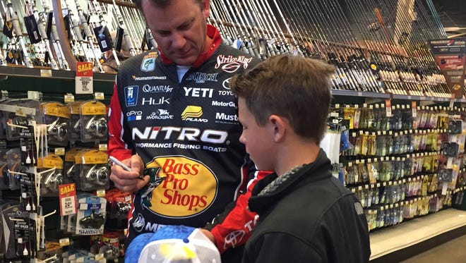Kevin VanDam signs a hat for a youngster recently at the Bossier City Bass Pro Shops. He'll compete in his 26th Bassmaster Classic this weekend.