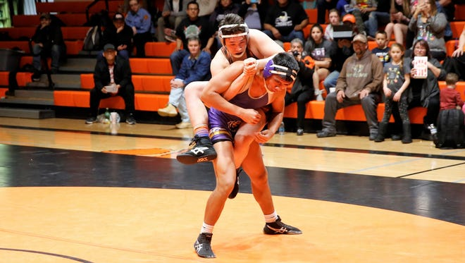 Aztec's Hunter Medina jumps on to the back of Kirtland Central's Isaac Thomas during the first period of their match in Thursday's District 1-5A wrestling opener at Lillywhite Gym in Aztec. Visit daily-times.com to see the latest sports photo galleries, video highlights and Saturday's basketball scores.