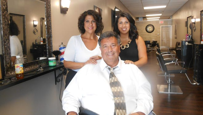 Rick Antelli, seated, flanked by wife, Laurie, at left and daughter Ashley inside Antelli Salon in Greece.