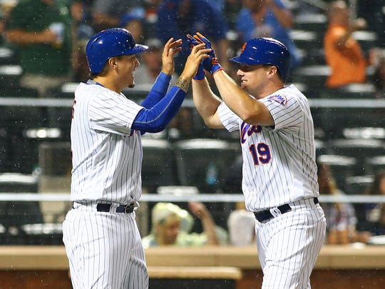 Mets right fielder Jay Bruce (19) is congratulated by second baseman Wilmer Flores (left) after hitting a two run home run against the Oakland Athletics during the sixth inning at Citi Field. Flores would homer in the ninth inning to give the Mets a walk-off win on Saturday, July 22, 2017.