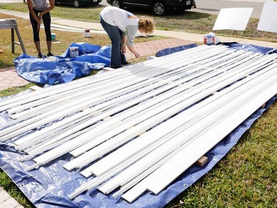 A Rebuilding Together volunteer paints trim outside