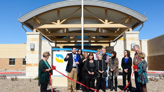 Chief Executive Officer Kyle Rockwell cuts a ribbon during the open house for the Reagan Memorial Hospital/Hickman Clinic Sunday in Big Lake. He is joined by hospital board members and staff.