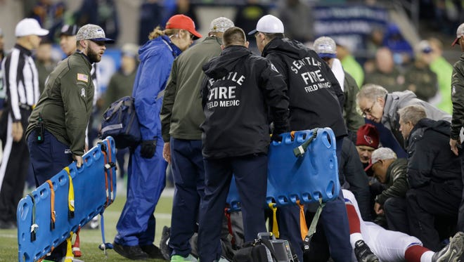 Backboards are brought in to take injured Arizona Cardinals' guard Mike Iupati off the field after a play against the Seattle Seahawks in the first half of an NFL football game, Sunday, Nov. 15, 2015, in Seattle.