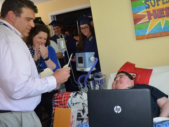 West Clermont Principal Randy Gebhardt and about 50 others pay a visit to senior Alex Click to present him with his graduation awards.