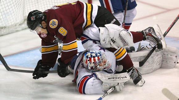 Chicago Wolves winger Shane Harper topples over Amerks goalie Andrey Makarov during this year's first-round playoff series.
