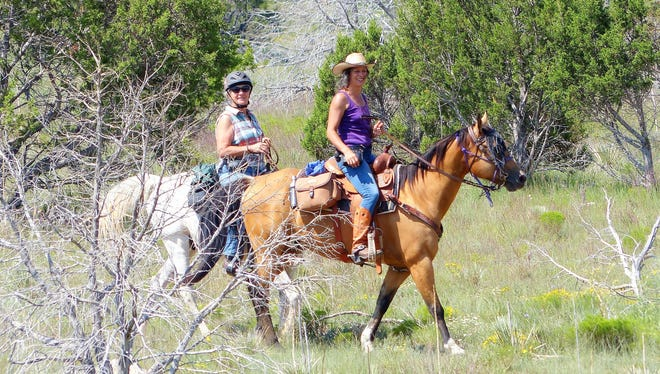 Two horsewomen ride the trails around Fort Stanton on a warm summer day in Lincoln County.