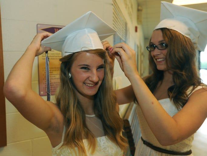 Excited graduates Bekah Lehman, 18, left, and Marissa Elmore, 18, help each prepare for ceremonies at Owen High School Saturday. John Coutlakis 6-14-14