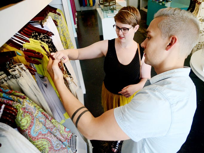 Cierra Hodo gets assistance from co-owner of Click Boutique and Gallery Jason Leviere Friday at the store's location on Front Street. Friday marked the sixth annual Mississippi Sales Tax Holiday. Clothing items purchased under $100 will be free from the usual seven percent sales tax.