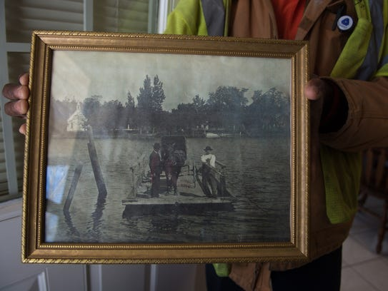 Terry Downing holds an old photograph of a past ferry,