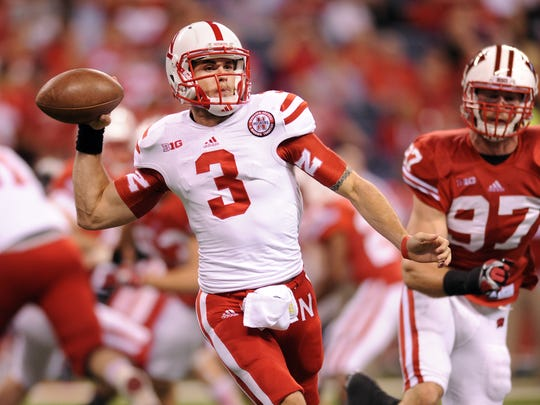 FILE - Nebraska's Taylor Martinez drops back to pass on the Wisconsin defense during the Big Ten Football Championship game  Dec. 1, 2012 at Lucas Oil Stadium.