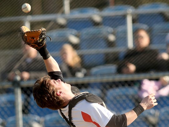 Central Kitsap's Austin McMinds makes a catch behind the plate for the out against Peninsula at the Fairgrounds on Tuesday.