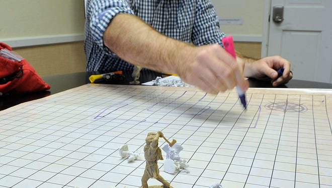 In this July 3, 2018 photo, Richard Stubbs explains how he incorporates tabletop role-playing games into his group therapy sessions at office in Medford, Ore. (Jamie Lusch/The Medford Mail Tribune via AP)