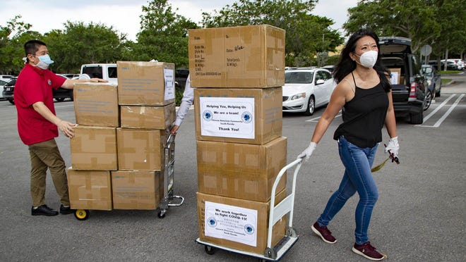 Rui Falcon, (right) and Lian Mo (left) members of the Chinese Association of Science, Education and Culture of South Florida, (CASEC) help deliver more than 20,000 N95 masks to Delray Medical Center in Delray Beach, Thursday, April 16, 2020.