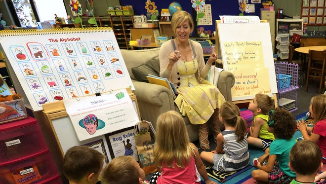 Kindergarten teacher Laura Willey talks with her new students on the first day of school at Wallace Elementary School on Thursday, Aug. 14, 2014.