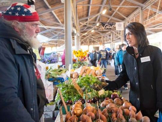 Vendor Dale Thorp of Rochester speaks with Republican Monroe County executive candidate Cheryl Dinolfo at the Public Market.