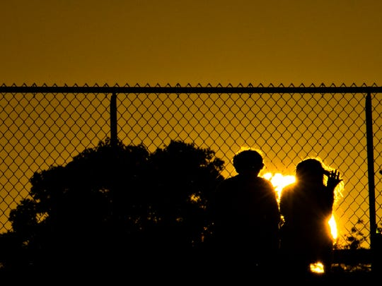 Fans look on as the sun sets before the AHSAA football game between Catholic and Dale County on Oct. 6, 2017, at Montgomery Catholic in Montgomery, Ala.