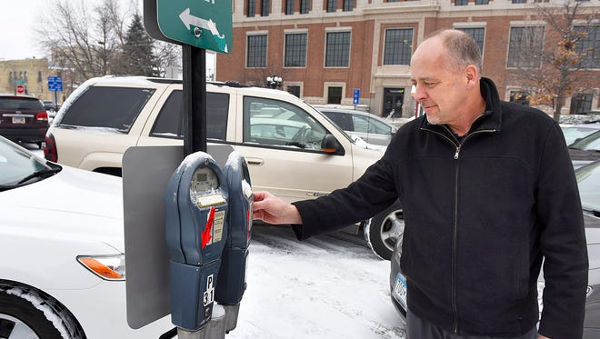 Kevin Olson, Sauk Rapids, puts money in the parking meter Wednesday, Jan. 20, outside the Stearns County Administration Building. St. Cloud will be installing 31 new parking meters in the Plaza Lot that will take both coins and credit cards.