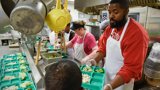 Cook Crystal Overboe, left, and Darius Cotton, sports and fitness coordinator, serve an evening meal to students Thursday, May 12, 2016, at the Southside Boys & Girls Club.