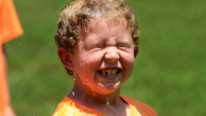 Tripp Lane smiles as water is poured on him Thursday afternoon during  Central District West Tennessee Cub Scouts Day Camp at First Cumberland Presbyterian Church.