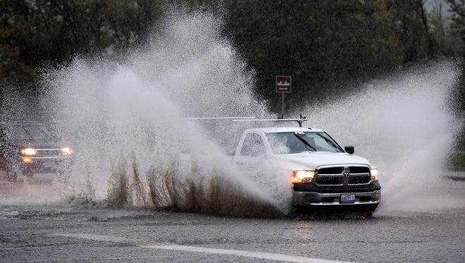 A motorist makes a wave of water while driving along Cliff Ave. during the rainstorm on Thursday.