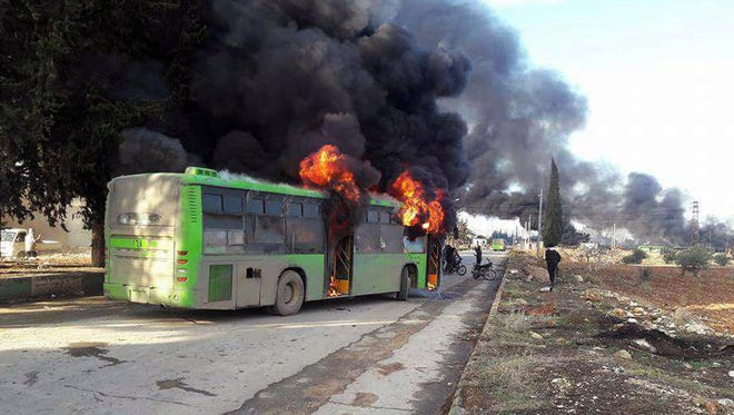 In this photo released by the Syrian official news agency SANA, smoke rises in green government buses, in Idlib province, Syria, Sunday, Dec. 18, 2016. Activists said militants have burned at least five buses assigned to evacuate wounded and sick people from two villages in northern Syria.