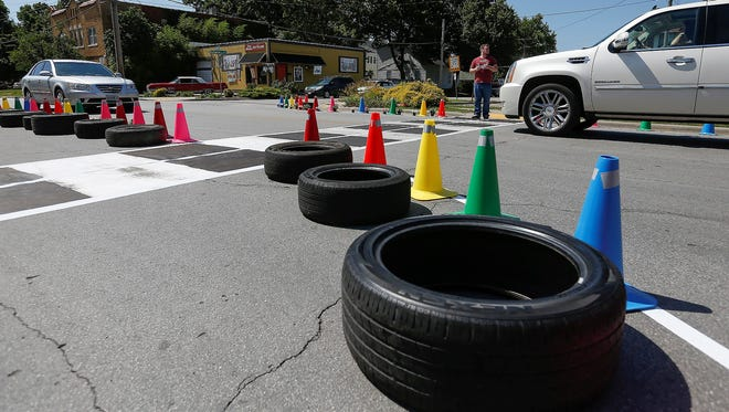 Brightly colored cones and tires lined East Cherry Street as part of a pop-up traffic calming project.