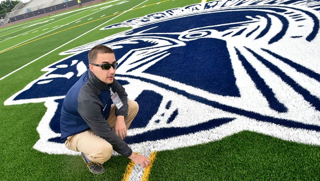 Jeremy Flores, CASHS athletic director, checks out the newly-installed turf. Repairs and renovations are complete at the turf and underway at the Trojan Stadium track on Wednesday, June 21, 2017.