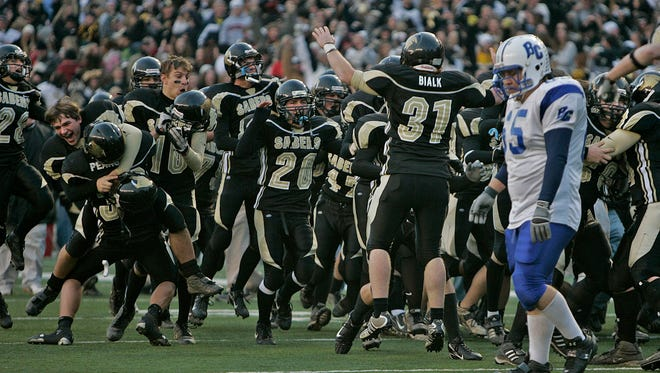 Brookfield Centrals' Jacob Glickstein walks off the field as the Franklin bench erupts in victory in overtime of their WIAA Division 2 State Football Championship game at Camp Randall in Madison, Friday, Nov, 17, 2006.