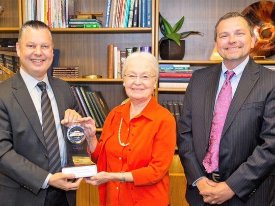 UTEP President Diana Natalicio on April 26 accepts Lockheed Martin Aeronautics' Quality Excellence Award from Daniel Pleshko, left, vice president of quality and mission success for Lockheed Martin, and Charles Akers, director of mission assurance for the company.