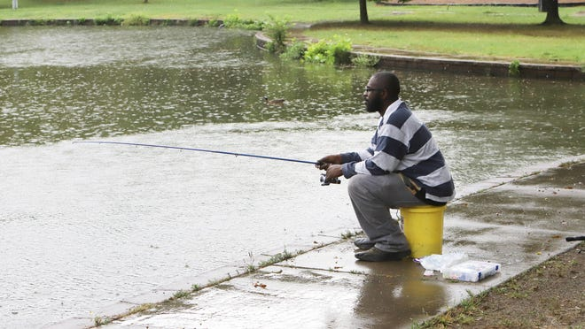 Carl Coney doesn't mind a little rain as he fishes for supper, Thursday, July 30, 2020, at Carol Ann Cross Park.